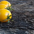 Stock Photo: Yellow tomatoes on wooden background
