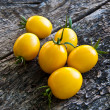 Yellow tomatoes on a wooden background — Stock Photo