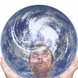 Man holds the earth and look up — Stockfoto