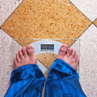A man is standing on a scale — Stockfoto