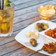 Mojito cocktail with snacks on wooden table — Stock Photo