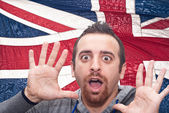 Young amazed man portrait with british flag — Stock Photo