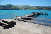 Old concrete pier with rails and table — Stock Photo