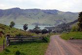 Gravel road and farm fence near bay — Stock Photo