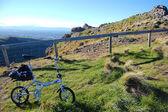 Folding bike on grass near fence — Stock Photo
