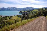 Camino de ripio rural con valla en las tierras de labrantío — Foto de Stock