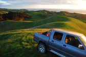 Car at green hill top rural area — Stock Photo