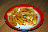 Fried banana at red metal plate — Stock Photo