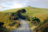 Gravel road turn left at rural area near water tank on hill top — Stock Photo