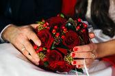 Mani di sposi tenendo un bouquet da sposa — Foto Stock