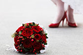 Wedding bouquet and bride's feet — Stock Photo