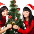 Two girls with champagne near Christmas tree — Stock Photo