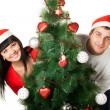 Man and woman looking out of Christmas tree — Foto Stock