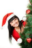 Vrouw in rode Glb kijken uit kerstboom — Stockfoto