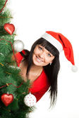 Woman in red cap looking out of Christmas tree — Stock Photo