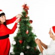 Man and woman decorating Christmas tree — Foto Stock