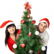 Man and woman looking out of Christmas tree — Stock Photo