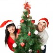 Stock Photo: Man and woman looking out of Christmas tree