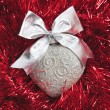 Silver Christmas heart on red tinsel — Stock Photo