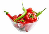 Red and green chili and bulgarian pepper in glass dish isolated — Stock Photo