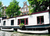 Floating house with boats in Amsterdam — Stock Photo