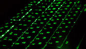 Green lighting keyboard in the dark — Stock Photo