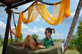 Young woman relaxing in hammock with tablet — Stock Photo