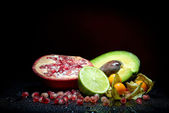 Fresh fruits with waterdrops on them and knife — Stock Photo