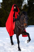 Beautiful woman with red cloak with horse outdoor in winter — Foto Stock