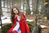 Beautiful woman with red cloak posing in the woods — Foto Stock