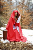 Beautiful woman with red cloak and suitcase — Stock Photo
