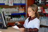 Young female pharmacist holding prescription — Stock Photo