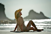Young woman sitting on the beach — Stock Photo