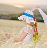 Young beautiful woman on golden cereal field in summer — Stock Photo