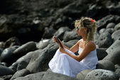 Young woman using tablet on rocky beach — Stock Photo