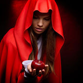 Beautiful woman with red cloak holding apple — ストック写真