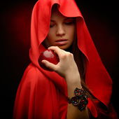 Beautiful woman with red cloak hoding apple — Stock Photo