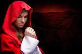 Beautiful woman with red cloak in studio — Stock Photo