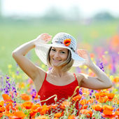 Young beautiful woman on flower field in summer — Stock Photo