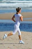 молодая женщина, бег на пляже летом — Стоковое фото