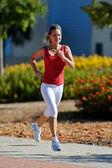 Jeune femme jogging dans le parc en été — Photo