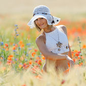 Young beautiful woman on golden wheat field in summer — Stock Photo