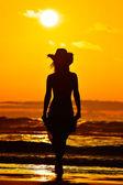 Silhouette de la jeune femme sur la plage en été — Photo