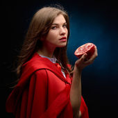Beautiful woman with red cloak holding pomegranate in studio — Stock Photo