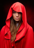 Beautiful woman with red cloak in studio — Stockfoto