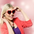 Valentine's day portrait of an attractive young blonde girl with heart shaped glasses well dressed wearing purple dress against pink background — Stock Photo #19130981