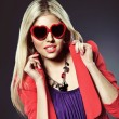 Valentine's day portrait of an attractive young blonde girl with heart shaped glasses well dressed — Stok fotoğraf