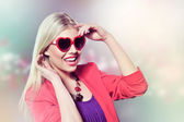 Valentine's day portrait of an attractive young blonde girl with heart shaped glasses well dressed wearing purple dress against pink background — Stock Photo