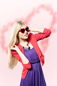 Valentine's day portrait of an attractive young blonde girl with heart shaped glasses — Stockfoto