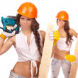 Gemini girls in orange helmets with an electric drill and electric saw on a white background. — Stock Photo #15654083